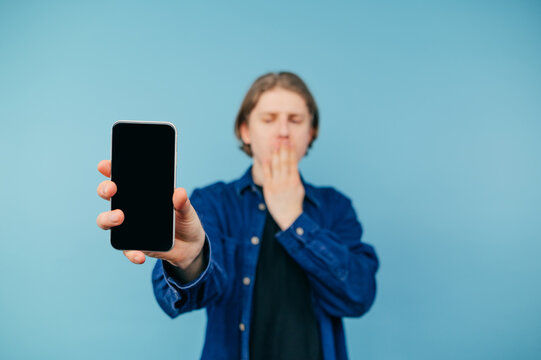 Shocked guy in a shirt stands on a blue background and shows a smartphone with a black blank screen to the camera, covering his face from surprise. Copy space