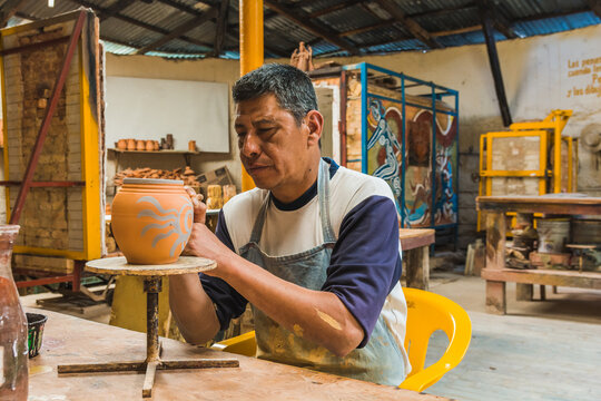 Mexican potter craftsman, working the clay with his hands in his workshop to create sculptures, vases, jugs, vases etc, using traditional methods.