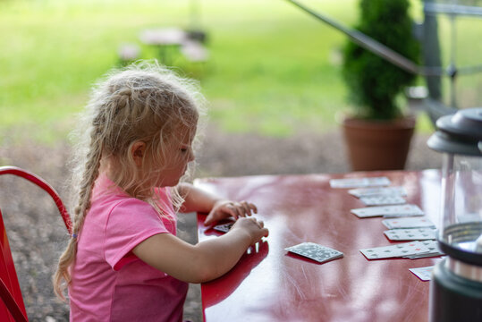 Little girl playing solitaire at an outdoor table
