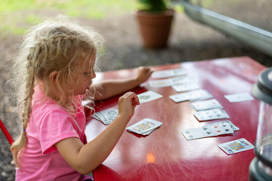 Child playing cards on a red table
