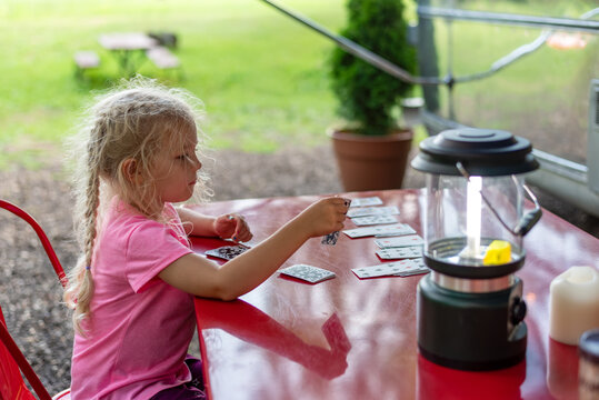 Little girl playing solitaire at a campsite
