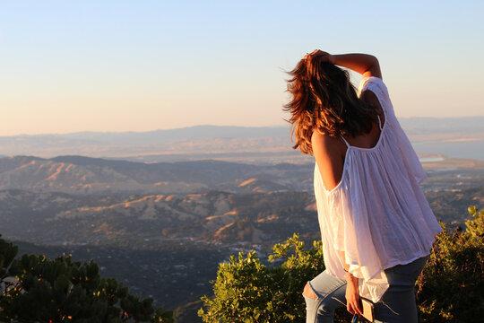 Woman in white overlooks mountain ledge