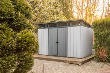 Fototapeta Modern summer house made of plastic. Gray garden shed for garden tools.  obraz