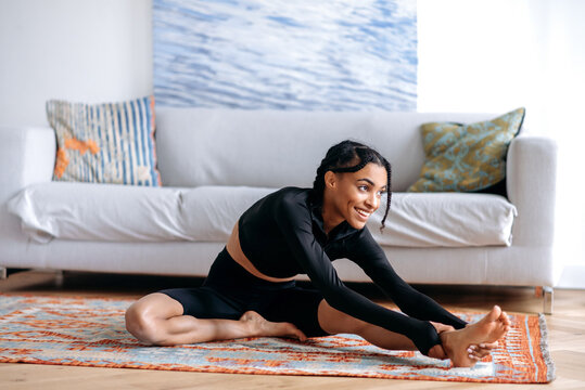 Satisfied young African American woman in black sportswear, doing fitness in living room on carpet, stretching her arms to her feet, doing back stretching, leads healthy lifestyle, looking away, smile