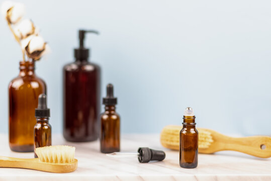 Selective focus aromatherapy background with amber glass bottles and natural brushes