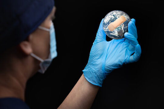 Nurse or Doctor Wearing Face Mask and Surgical Gloves Holding Bandaged Planet Earth