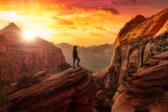 Adventurous Woman at the edge of a cliff is looking at a beautiful landscape view in the Canyon. Sunset Sky Art Render. Taken in Zion National Park, Utah, United States.