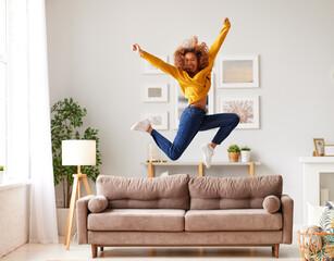Fototapeta Happy african american teen girl jumping on sofa while having fun on weekend at home obraz
