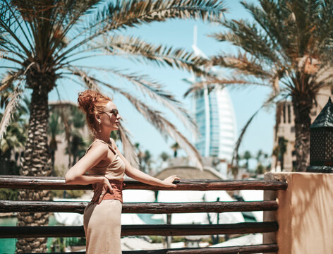 Rich luxury tourist woman in summer dress is enjoying sightseeing tour during vacation in Dubai in United Arab Emirates. Luxury and comfortable tourism season in UAE cityscapes