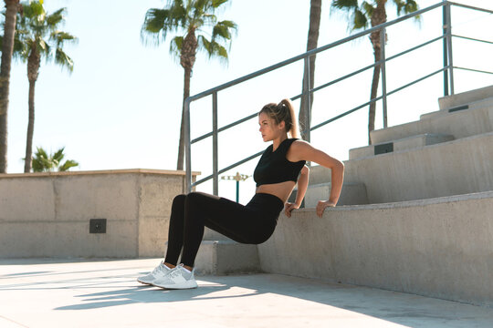 Athletic woman is doing triceps dip during summer calisthenic workout