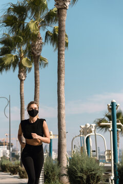 Athletic woman wearing face mask is running during her summer jogging workout