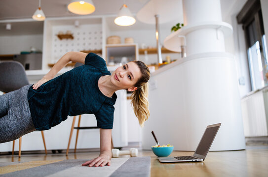 Beautiful young woman doing yoga, fitness exercise at home