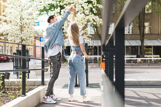 Young sensual and loving couple dancing during their date on a city street