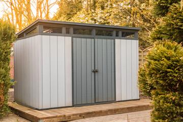 Fototapeta Modern summer house made of plastic. Gray garden shed for garden tools.gray garden shed made of plastic. Modern tool shed obraz