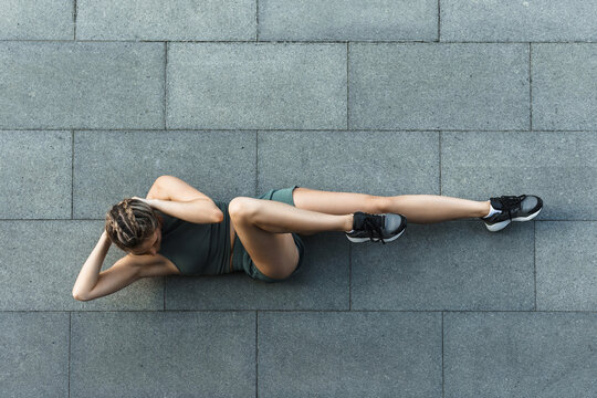 Athletic woman doing abdominal crunches exercise on concrete floor