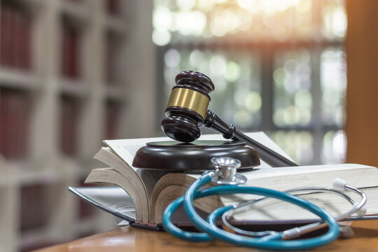 Forensic medicine science, criminalistics legal investigation or medical practice justice concept with judge gavel on law text book for criminal and civil laws in school class or library