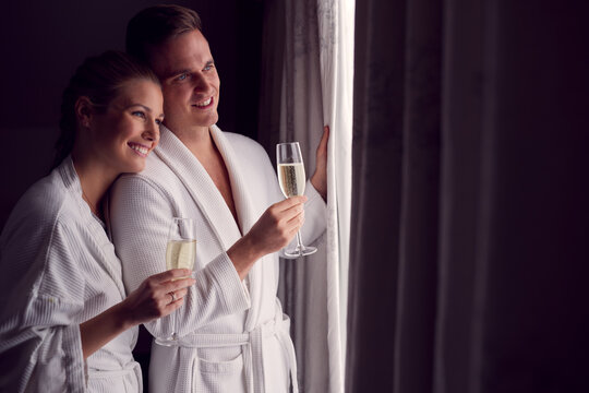 Couple Wearing Bathrobes On Romantic Hotel Break Standing By Open Curtains With Glasses Of Champagne