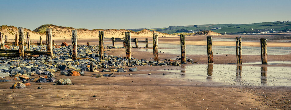 Beach scenery landscape at low tide with old breakwater and sand dunes