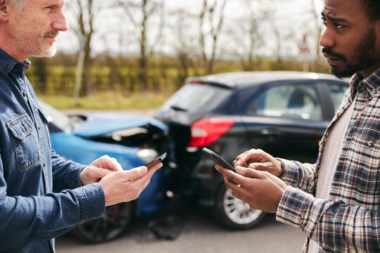 Senior Male Driver Exchanges Car Insurance Details With Younger Motorist After Road Traffic Accident