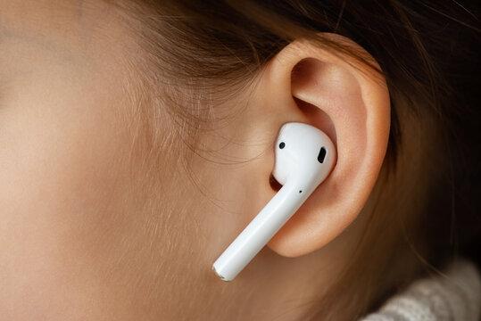 Wireless earphone in the girl's ear.