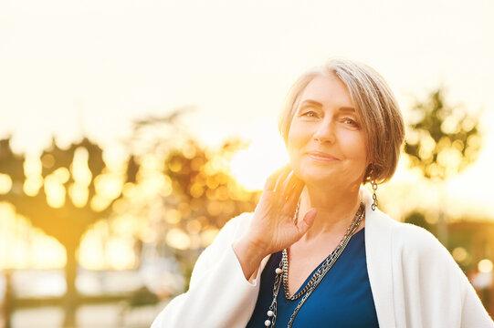 Outdoor portrait of beautiful and elegant mature woman posing in sunlight