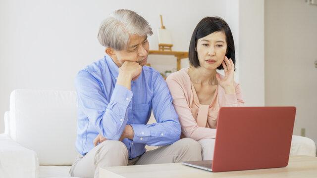 パソコンをしながら考え事をする中高年夫婦