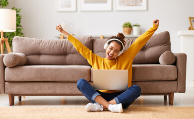 Fototapeta Overjoyed african american female in headphones sitting on floor and celebrating success while working remotely or studying online obraz