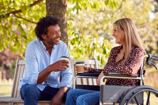 Mature Couple With Woman Sitting In Wheelchair Talking And Drinking Coffee In Park Together