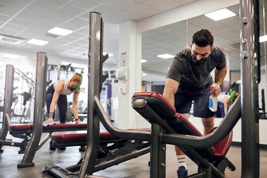 Gym employees disinfecting equipment during Coronavirus pandemic wearing face masks