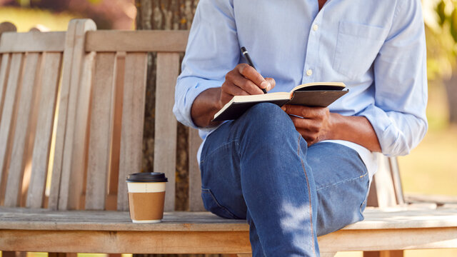 Close Up Of Man With Takeaway Coffee Sitting On Park Bench Under Tree Writing In Notebook