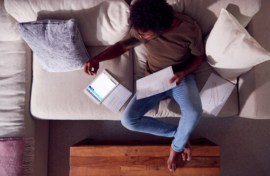 Overhead Shot Of Man Working From Home Sitting On Sofa Reviewing Documents Using Digital Tablet