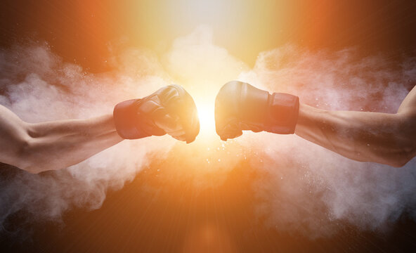 Mma fight, close up of two fists hitting each other over dark, dramatic sky with copy space.
