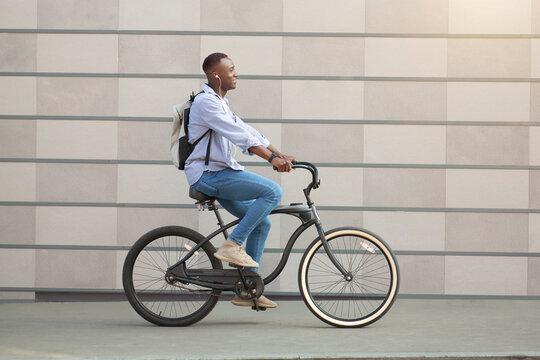 Side view of cool black guy with earphones racing on his bicycle near brick wall downtown