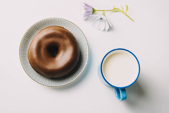 Donut de chocolate fresco delicioso sobre fondo blanco. Apetitosa y sabrosa rosquilla glaseada lista para comer con una taza de leche fresca