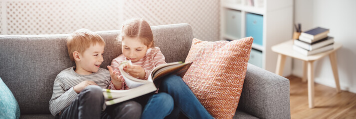 Fototapeta Cute children sitting on the soft sofa and reading books
