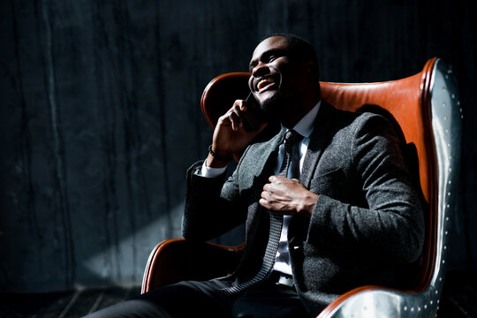 Stylish african american businessman sits on a chair in the office and communicates on the phone smiling