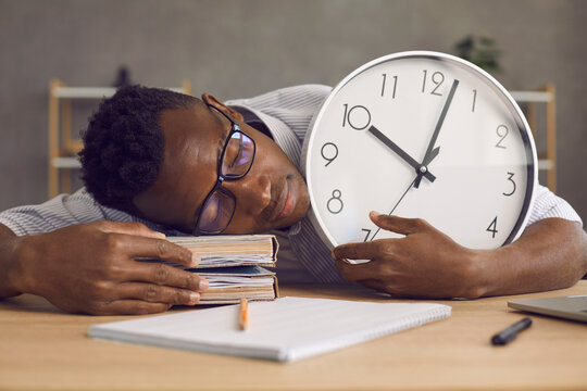 Tired young black man exhausted after preparing for exam hugs clock, lays head on books and falls asleep. Irresponsible lazy African student sleeping peacefully at desk not knowing he's late for class