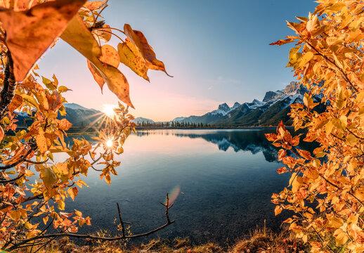 Sunrise on mountain range and golden leaves covered in Rundle Forebay Reservoir