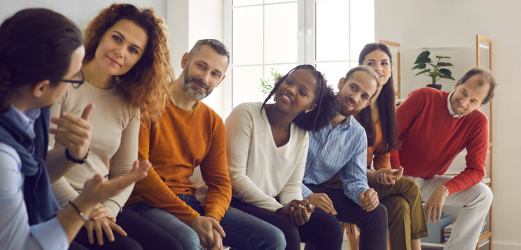 Group of interracial people sit in a row and listen with interest to a man telling his story. People communicate at group therapy meetings or meet competitors while sitting in line for an interview.