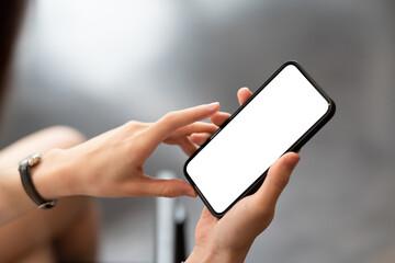 Fototapeta Close up woman hand holding a smartphone blank white screen. obraz