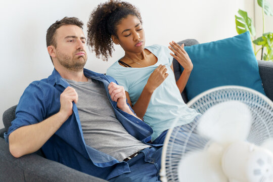 Mixed race couple trying to relief from summer heat wave