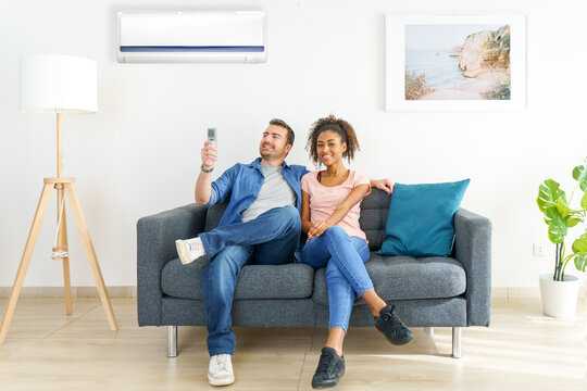 Mixed race couple relaxing under the air conditioner
