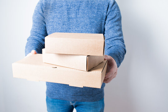 Young anonymous adult delivering three cardboard boxes, with white background