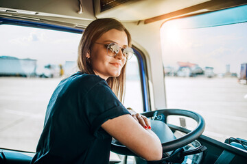 Portrait of beautiful young woman professional truck driver sitting and driving big truck. Inside...
