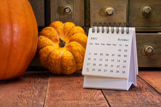 October 2021 - spiral desktop calendar on a weathered barn wood table with rustic apothecary drawers, pumpkin and squash in background, time and business concept