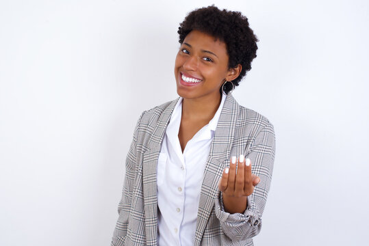 African American businesswoman with curly bushy hair wears  formal clothes over white background inviting to come with hand. Happy that you came