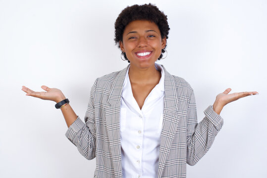 Cheerful cheery optimistic African American businesswoman with curly bushy hair wears  formal clothes over white background holding two palms copy space