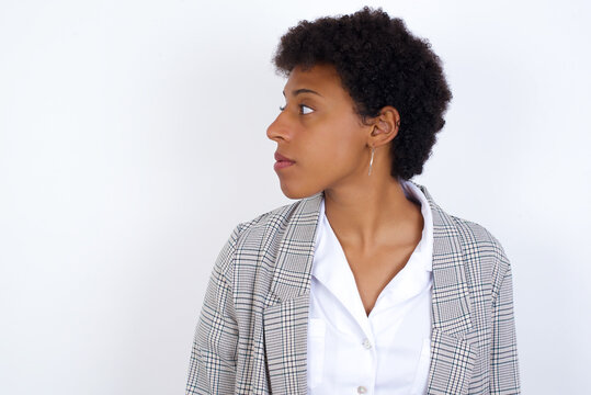 Close up side profile photo African American businesswoman with curly bushy hair wears  formal clothes over white background not smiling attentive listen concentrated