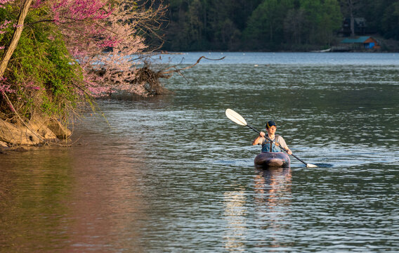 Caucasian man wearing PFD paddling towards the camera on a spring evening on a calm lake