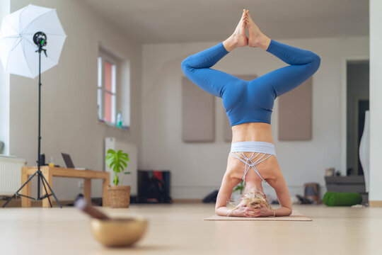 Backstage of a yoga photo shooting. The instructor performs a pose on the head, and in the background you can see the flash of the photo shooting.